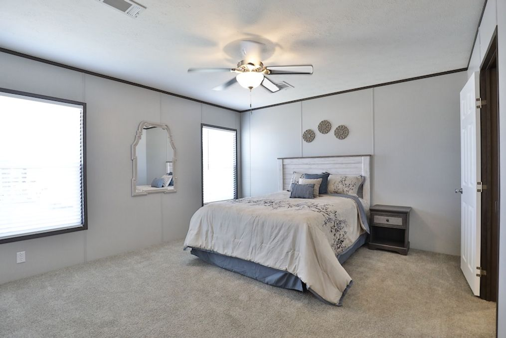 The BREEZE FARMHOUSE Master Bedroom. This Manufactured Mobile Home features 3 bedrooms and 2 baths.