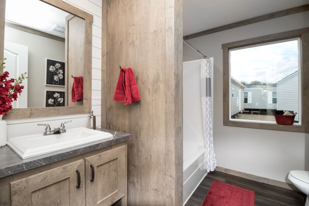 The FARMHOUSE 4 Guest Bathroom. This Manufactured Mobile Home features 4 bedrooms and 2 baths.